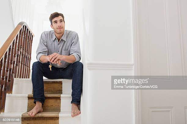 man sitting and contemplating on steps - only young men stock pictures, royalty-free photos & images