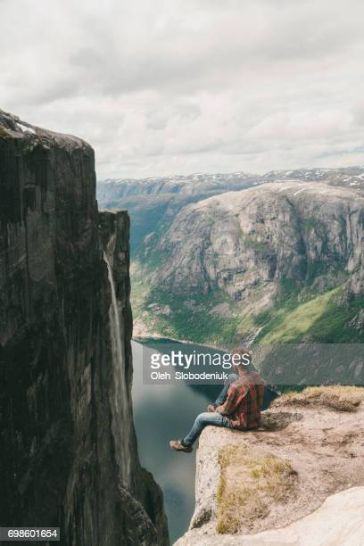 Man sitting and looking at scenic view of Lysefjorden from Kjerag mountain