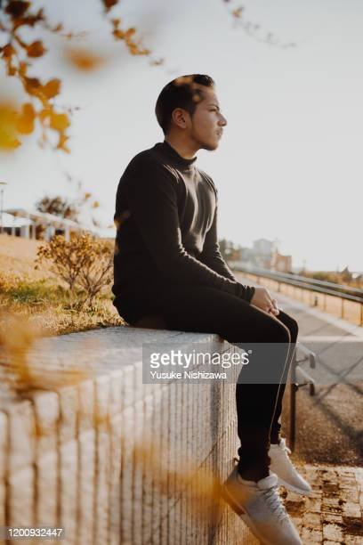 a man sitting and looking far away - yusuke nishizawa stock pictures, royalty-free photos & images