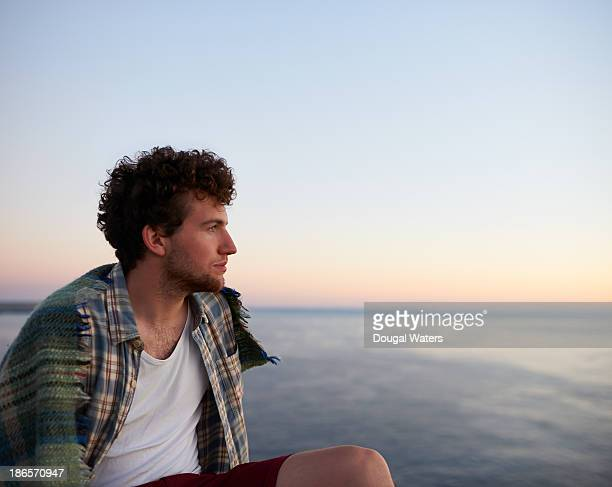 Man sitting and looking out to sea.