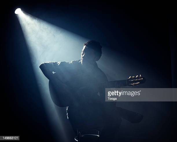 Man sitting and playing acoustic guitar