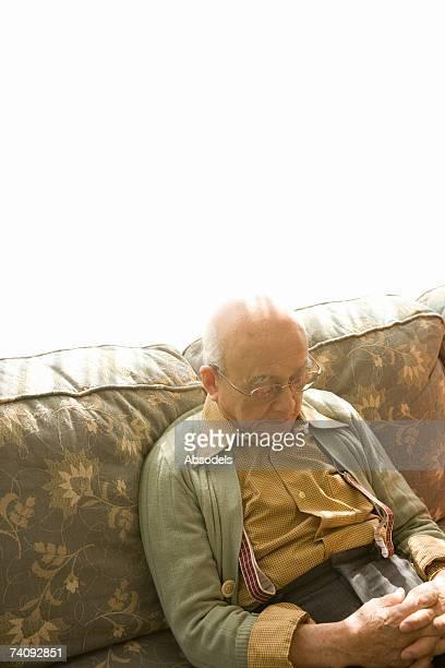 A man sitting and sleeping on a sofa