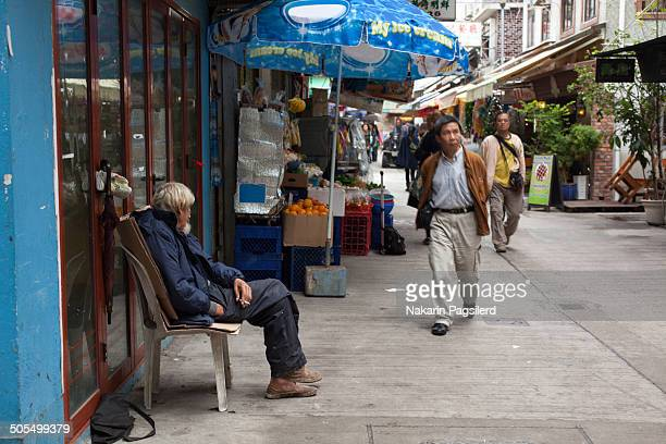 CONTENT] Man sitting and watch on Yung Shue Wan Main St