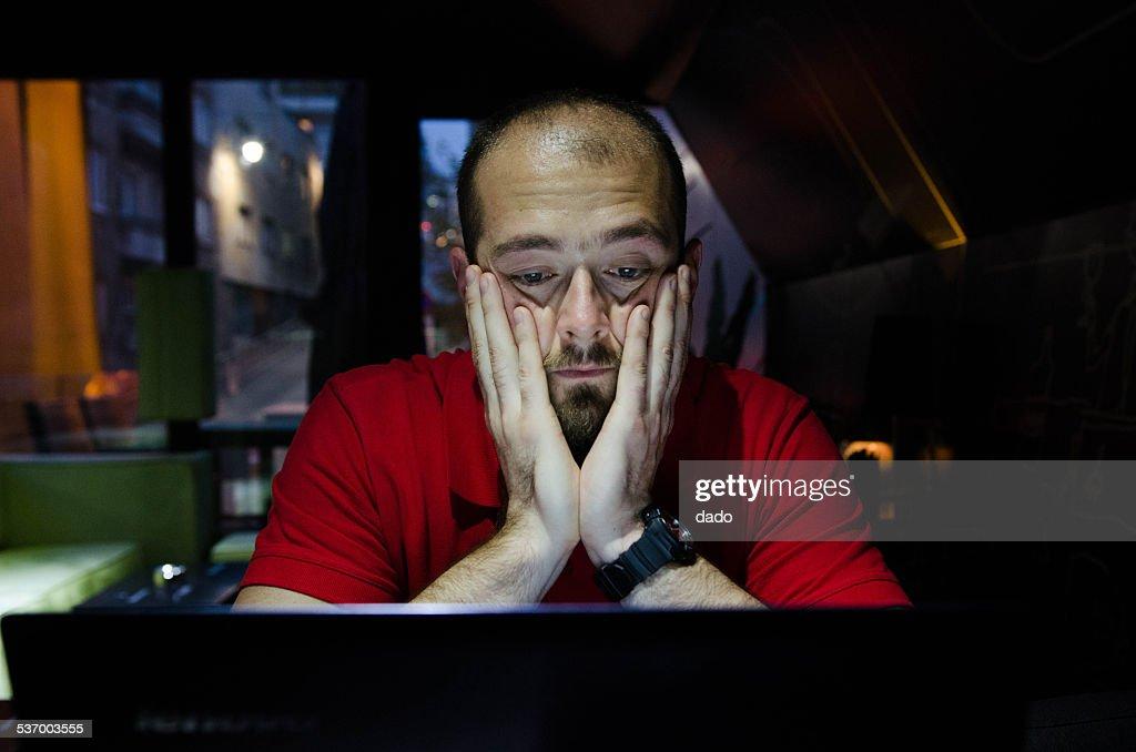 Man sitting and watching at laptop : Stock Photo