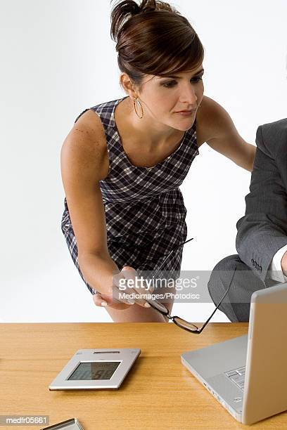 Man sitting and woman leaning over table with computer, close-up