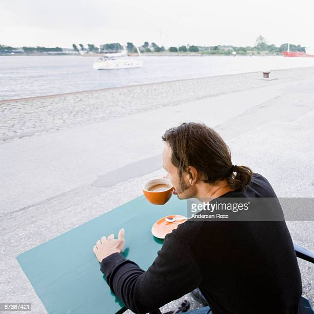 Man sitting at a cafe drinking coffee