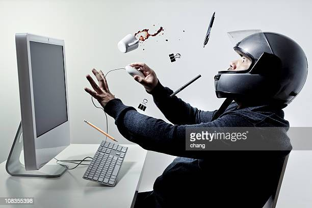 Man sitting at a computer wearing motorcycle helmet