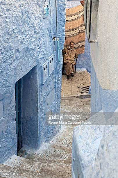 Man sitting at a doorway of a house in the blue medina of Chefchaouen. Morocco. 2012