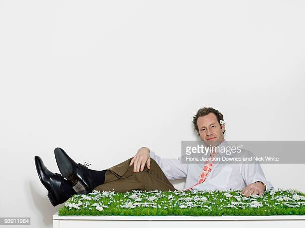 A man sitting at a grassy desk