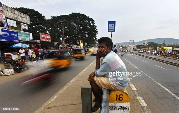 Man sitting at a road divider as vehicles pass by on October 10, 2014 in Visakhapatnam, India. Cyclone Hudhud, building over the Bay of Bengal, was...