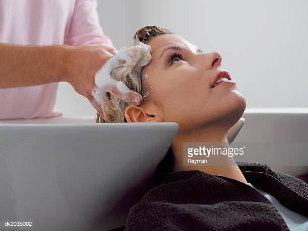 Man Sitting at a Sink Having His Hair Washed by a Hairdresser