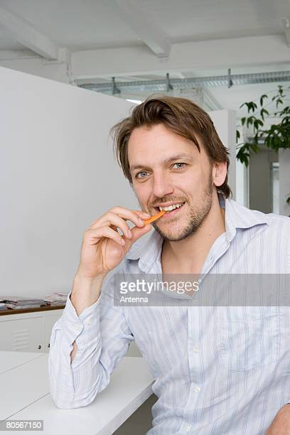 A man sitting at a table and eating a carrot stick