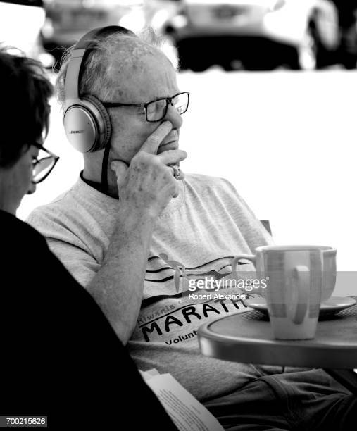 A man sitting at a table at an outdoor cafe in Aspen Colorado enjoys listening to music from his Bose wireless headphones
