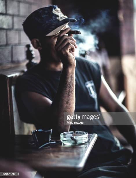 Man sitting at a table in a bar smoking a cigar.