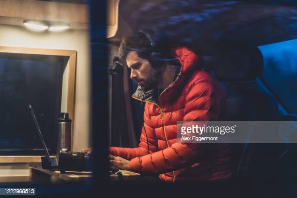 a man sitting at a table in his campervan working on his laptop. - photographer stock pictures, royalty-free photos & images
