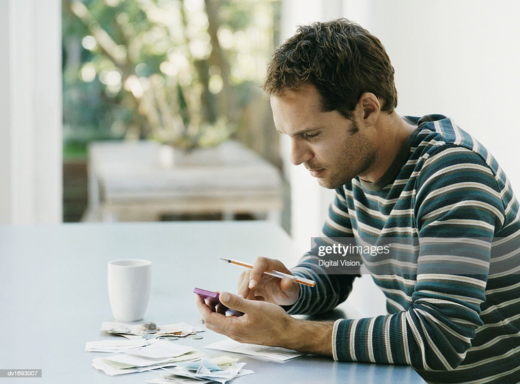 Man Sitting at a Table Using a Calculator : Stock Photo