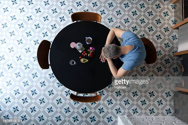 a man sitting at a table with his head resting on his arms, directly above - einsamkeit stock-fotos und bilder