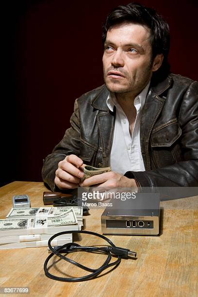 A man sitting at a table with stacks of money, a mobile phone and a hard drive