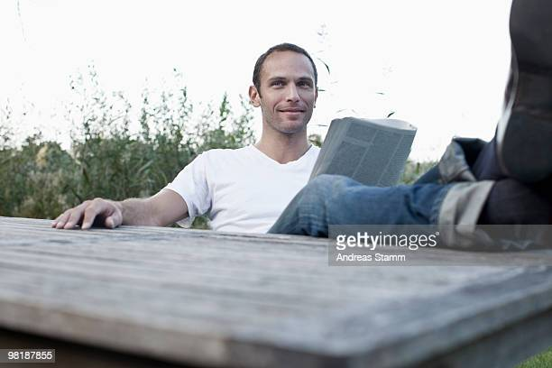 A man sitting at an outdoor table reading a magazine, non-urban scene