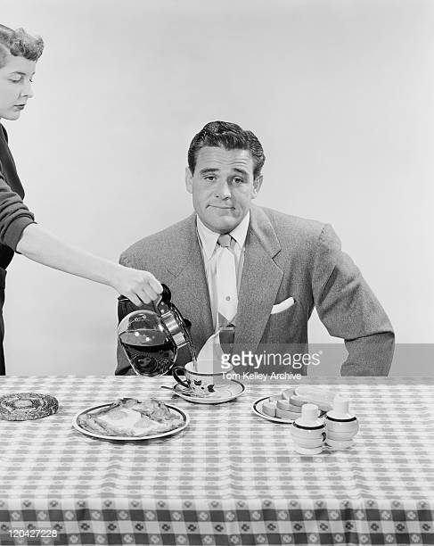 Man sitting at breakfast table, woman pouring black tea in cup