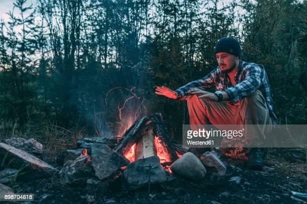 man sitting at campfire in rural landscape - überleben stock-fotos und bilder
