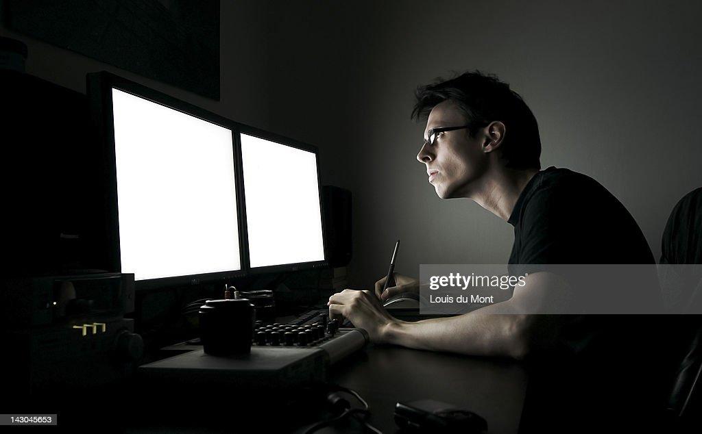 Man sitting at computer desk at night : Stock Photo