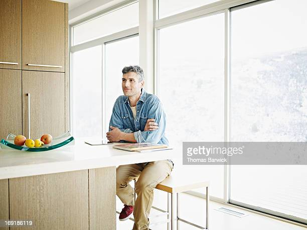 Man sitting at counter in contemporary home