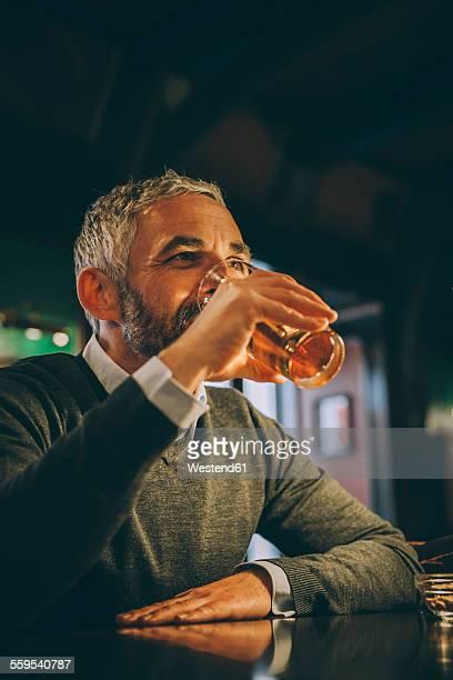 Man sitting at counter of a pub drinking beer