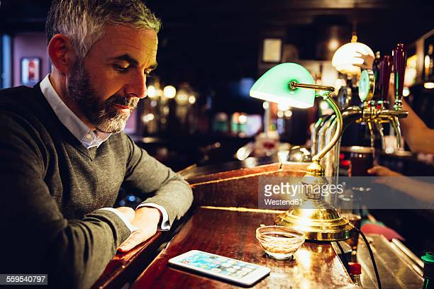 Man sitting at counter of a pub looking at his smartphone
