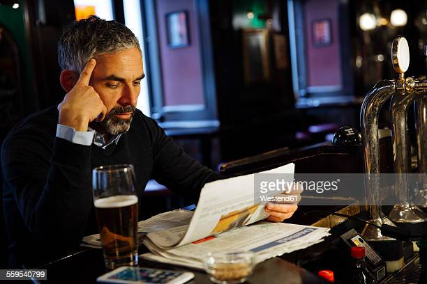 Man sitting at counter of a pub reading newspaper