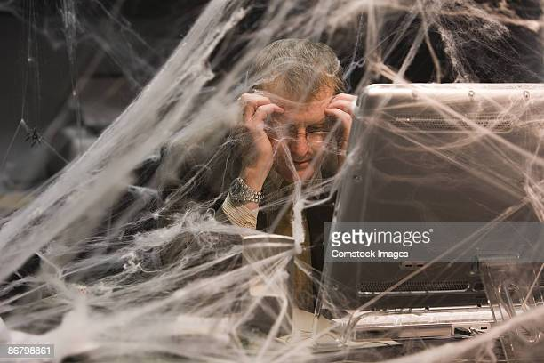 Man sitting at desk covered in cobwebs