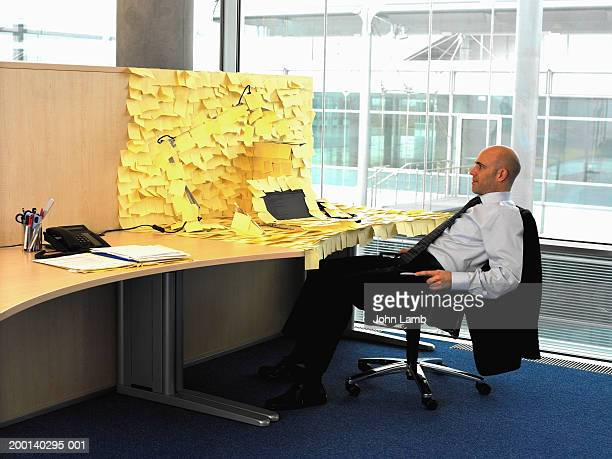 man sitting at desk covered in yellow memo notes - grupo grande de objetos - fotografias e filmes do acervo