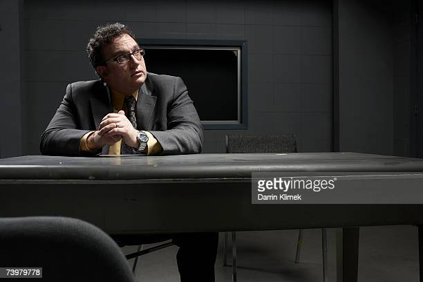 Man sitting at desk in interrogation room, looking away