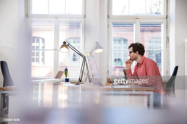 man sitting at desk in office - focus on background stock pictures, royalty-free photos & images