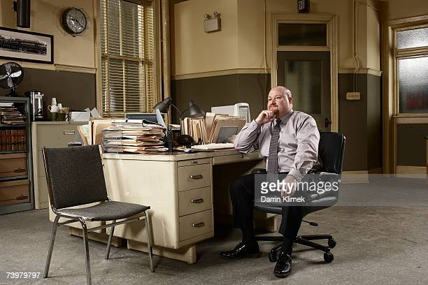 man sitting at desk in office - detective stock pictures, royalty-free photos & images