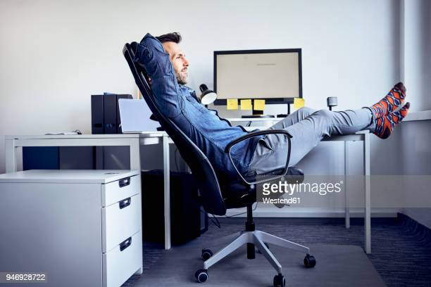 man sitting at desk in office relaxing - office chair stock pictures, royalty-free photos & images