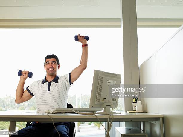 Man sitting at desk lifting weights, smiling