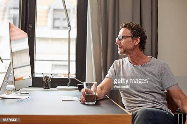 man sitting at desk looking at computer - 50 54 jahre stock-fotos und bilder