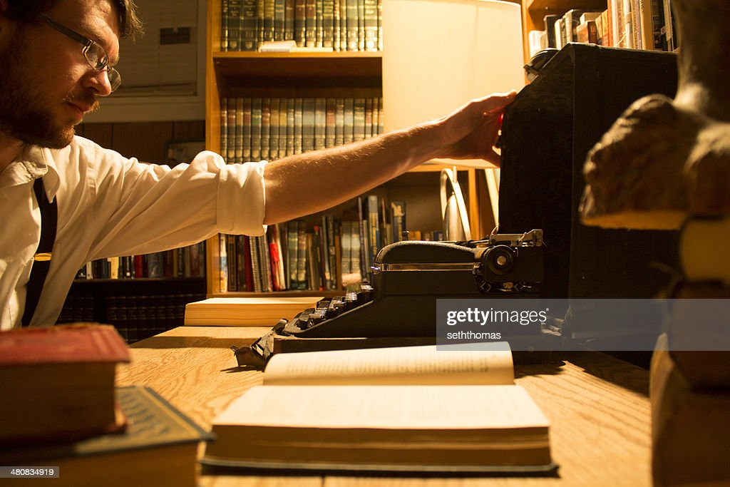 Man sitting at desk opening a typewriter : Stock Photo