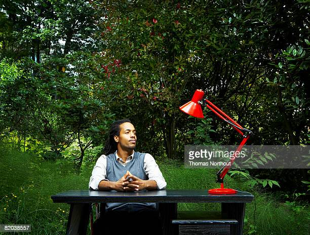 Man sitting at desk out in nature