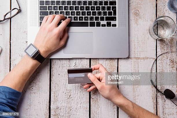 Man sitting at desk paying online with credit card