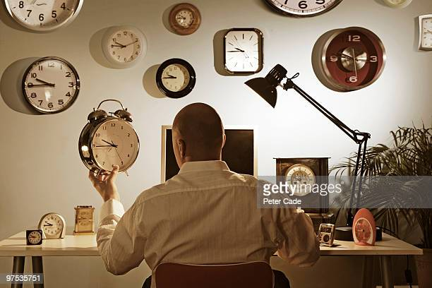 man sitting at desk surrounded by clocks
