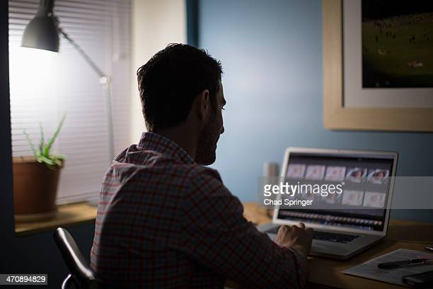 Man sitting at desk using laptop