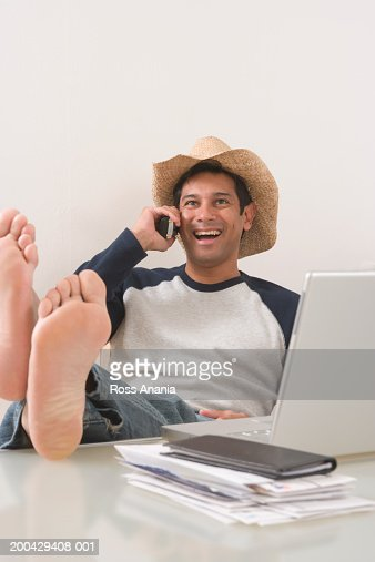 Man Sitting At Desk Using Phone And Laptop Feet On Desk