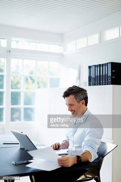 Man sitting at desk with laptop computer and paperwork
