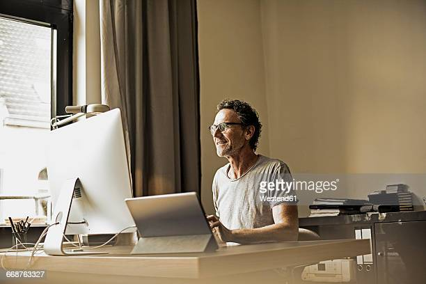 Man sitting at desk working with computer