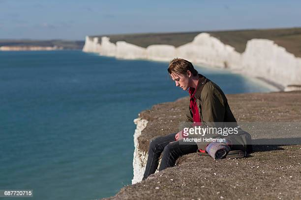 Man sitting at edge of cliff