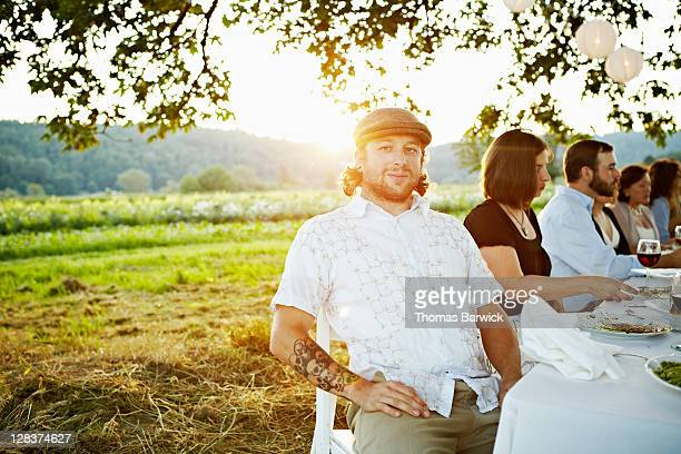 Man sitting at end of outdoor table at sunset