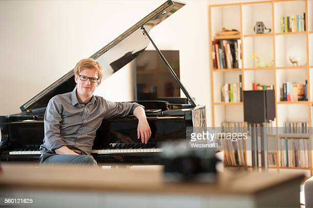 man sitting at grand piano - pianist front stock pictures, royalty-free photos & images