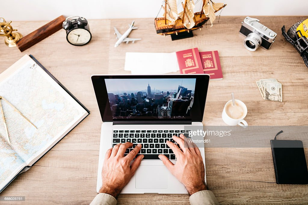 Man sitting at his desk planning his next journey : Stock Photo